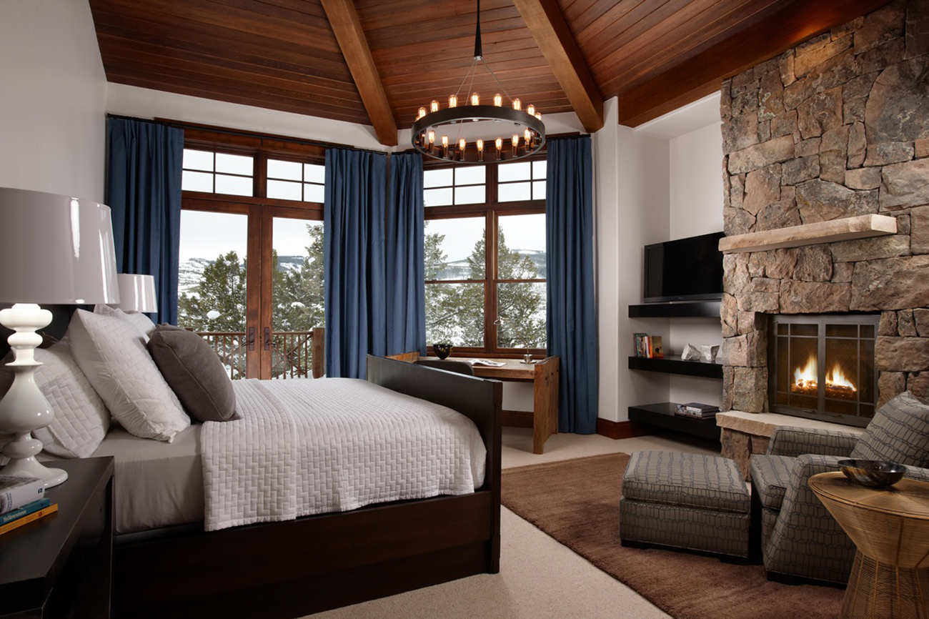 A cozy bedroom combines views, contemporary features, and mountain style.